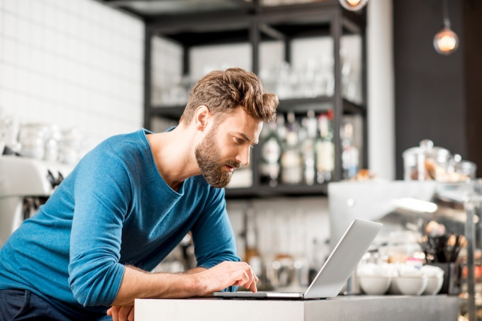 Male restaurant owner in restaurant kitchen looking through reports on laptop