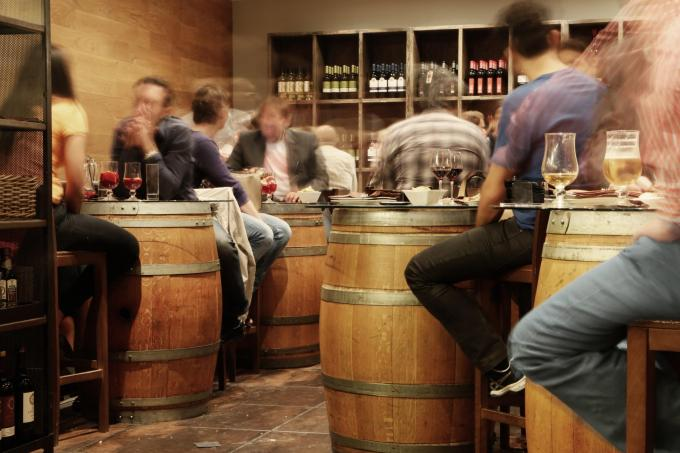 time-lapse photo of guests at busy restaurant sitting at beer barrel tables